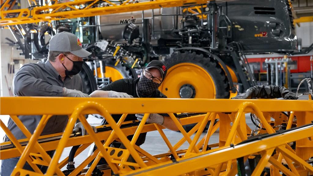 maintenance men working on hagie sprayer equipment